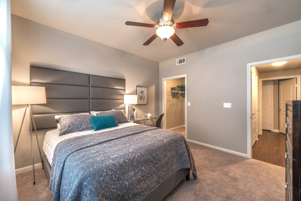 Model apartment's master bedroom with plush carpeting and a walk-in closet at Olympus Las Colinas in Irving, Texas