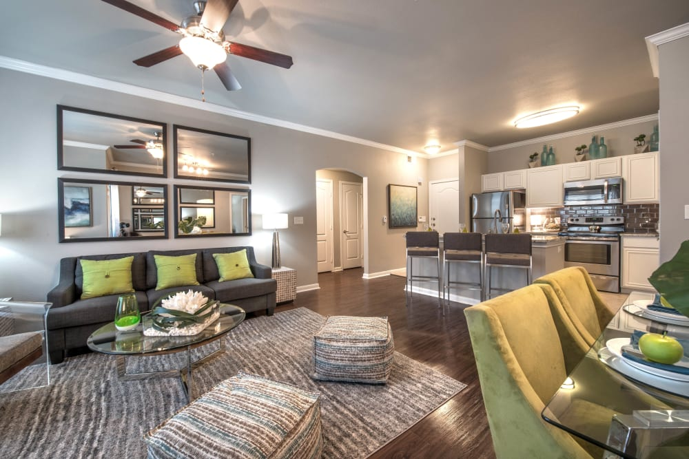 Model apartment's living space with a ceiling fan and hardwood floors at Olympus Las Colinas in Irving, Texas