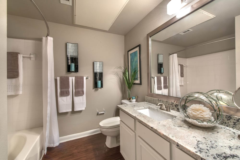 Ample counter space and hardwood flooring in a model home's bathroom at Olympus Las Colinas in Irving, Texas