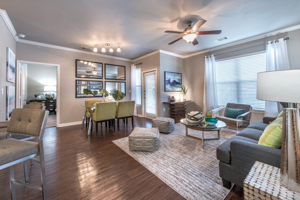 Well-furnished living area with a ceiling fan in a model apartment at Olympus Las Colinas in Irving, Texas