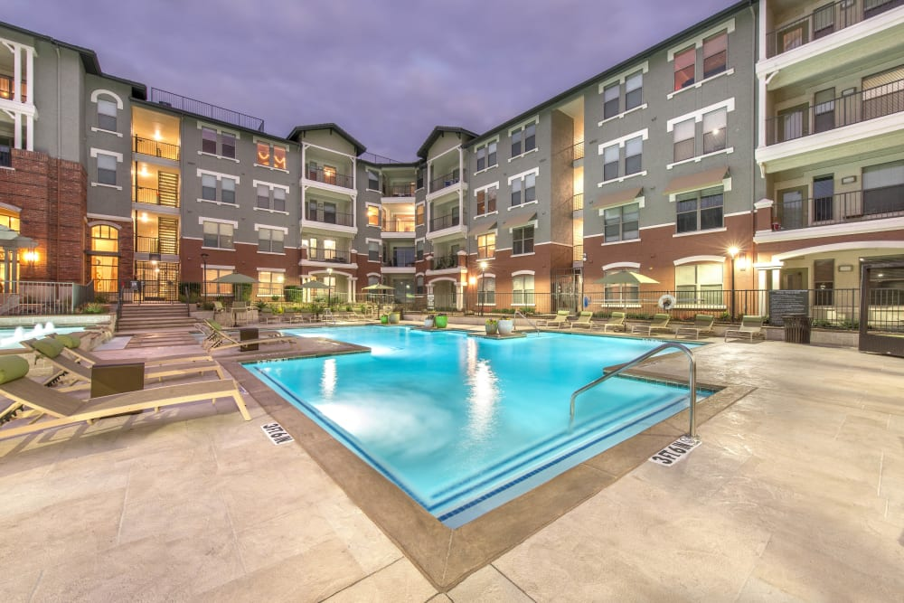 Dusk view of the swimming pool area at Olympus Las Colinas in Irving, Texas