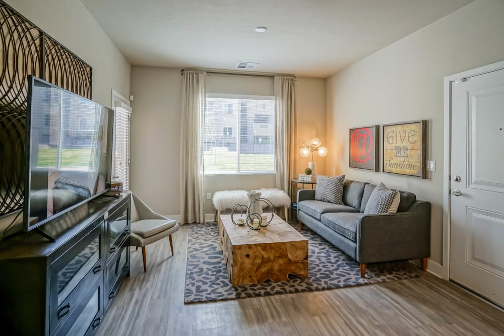 Bay window and hardwood floors in a model apartment's living area at Olympus Northpoint in Albuquerque, New Mexico