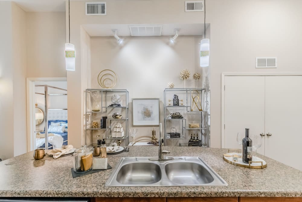 Urban style kitchen with granite countertop in model home at Olympus Boulevard in Frisco, Texas