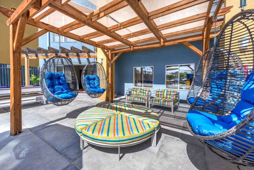 Hanging basked chairs under a pergola at one of the outdoor lounge areas at Olympus Solaire in Albuquerque, New Mexico