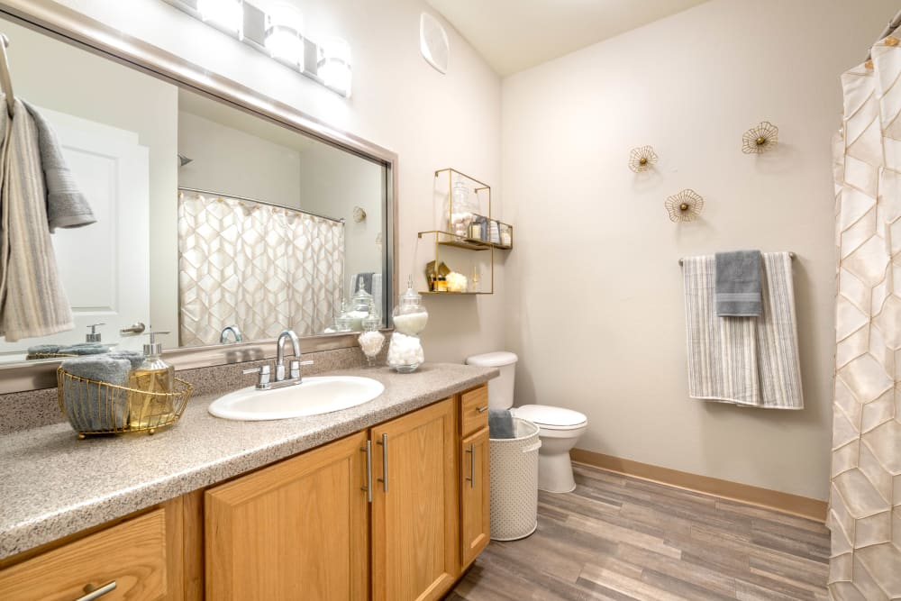 Oversized vanity mirror and a quartz countertop in a model apartment's bathroom at Olympus Solaire in Albuquerque, New Mexico