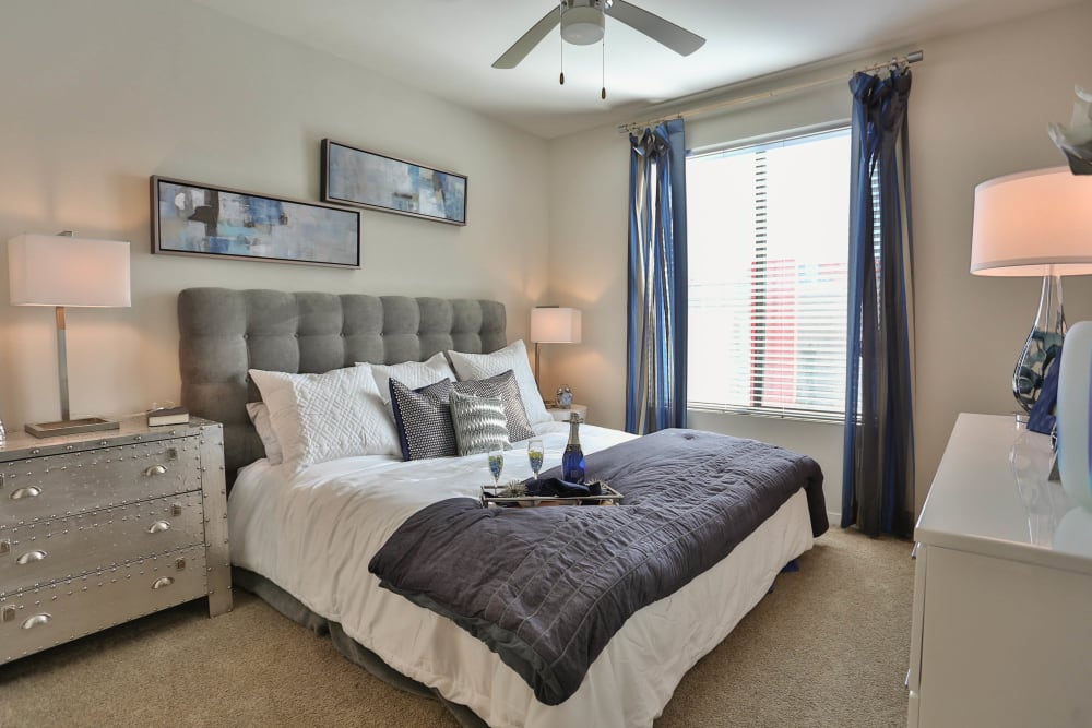 Plush carpeting and a ceiling fan in the well-furnished master bedroom of a model apartment at Olympus Steelyard in Chandler, Arizona