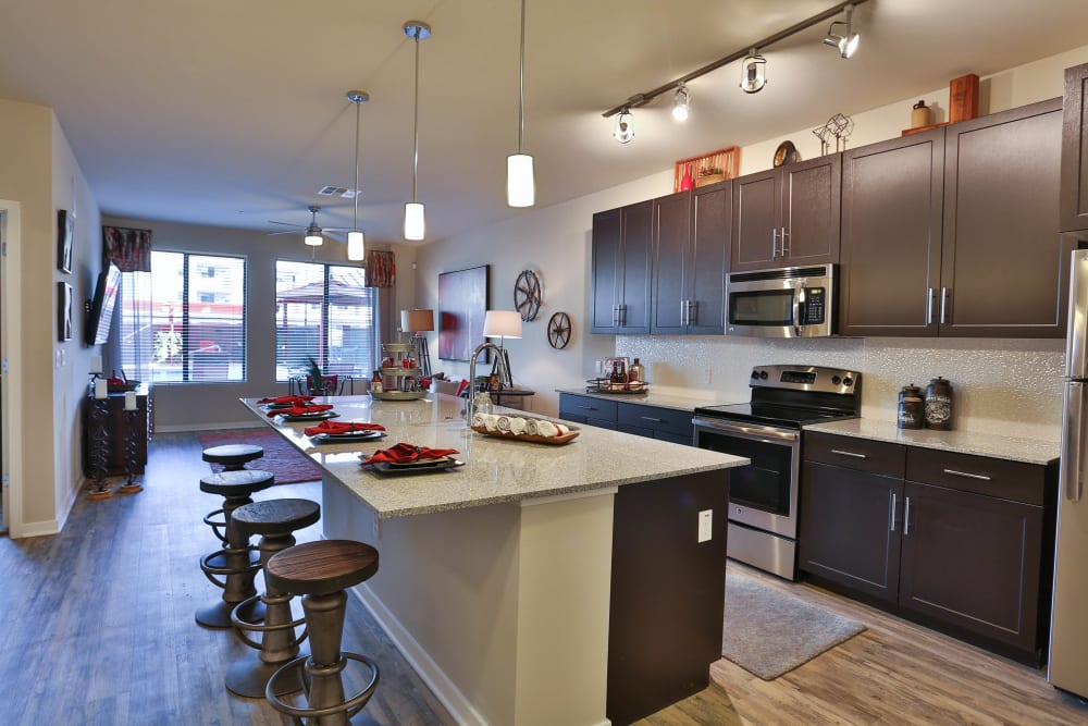 Model home's open-concept kitchen with stainless-steel appliances and granite countertops at Olympus Steelyard in Chandler, Arizona