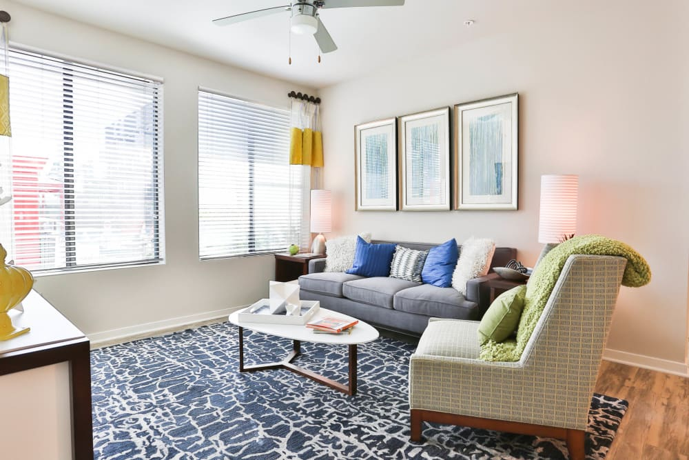 Bay windows and a ceiling fan in the living area of a model apartment at Olympus Steelyard in Chandler, Arizona