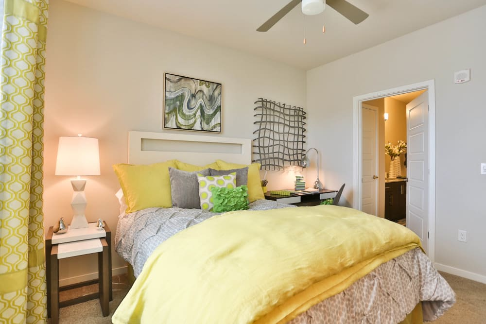 Brightly decorated master bedroom with an en suite bathroom in a model home at Olympus Steelyard in Chandler, Arizona
