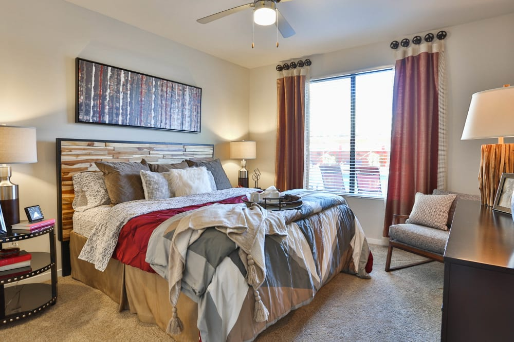 Model apartment's master bedroom with plush carpeting and draped windows at Olympus Steelyard in Chandler, Arizona