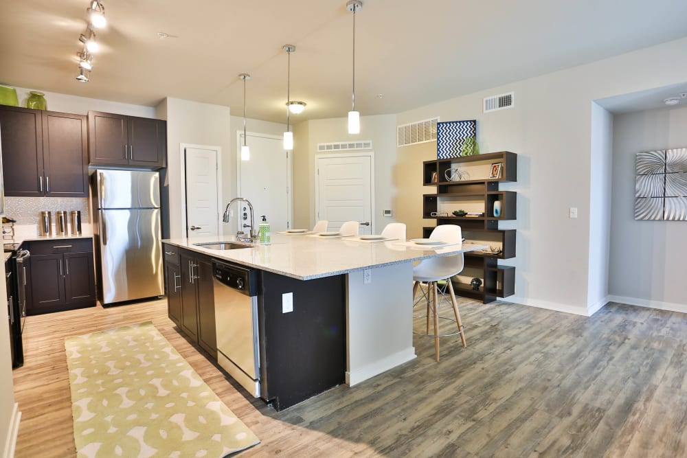 Island with a granite countertop in a model home's kitchen at Olympus Steelyard in Chandler, Arizona