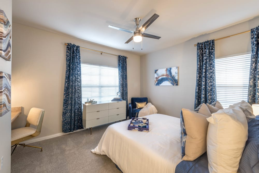 Model bedroom with draped bay windows and plush carpeting at Olympus Stone Glen in Keller, Texas