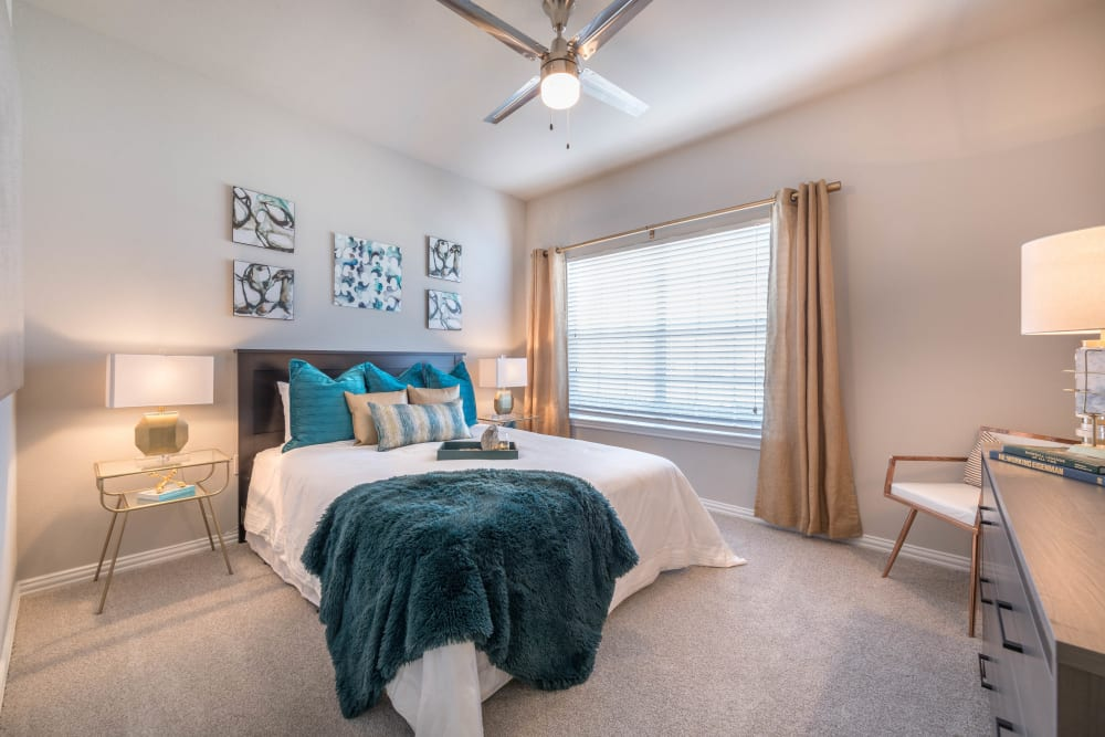 Plush carpeting and a ceiling fan in the spacious master bedroom of a model apartment at Olympus Stone Glen in Keller, Texas