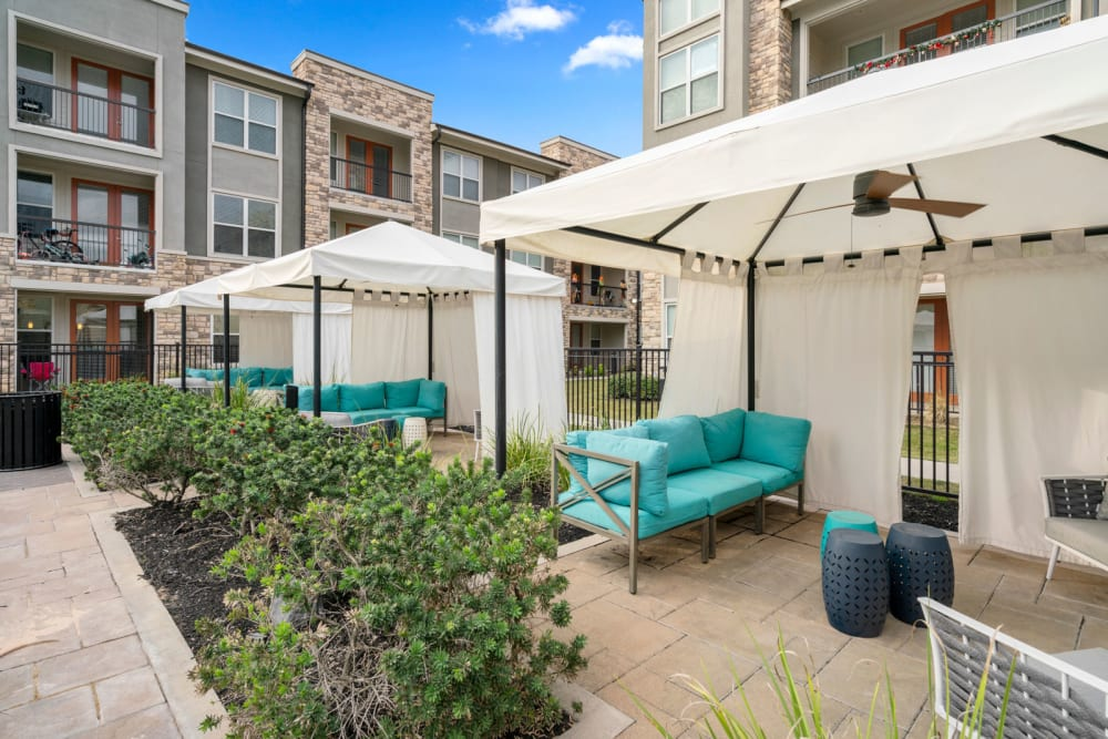 Private cabanas with fans by pool at Olympus Grand Crossing in Katy, Texas
