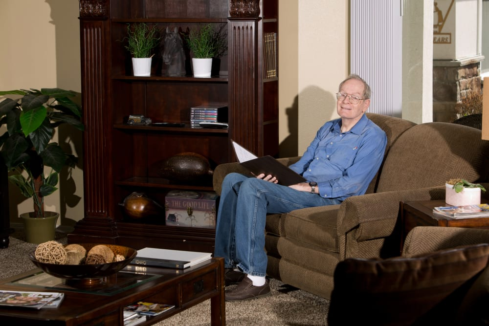 resident reading a book on a comfortable sofa