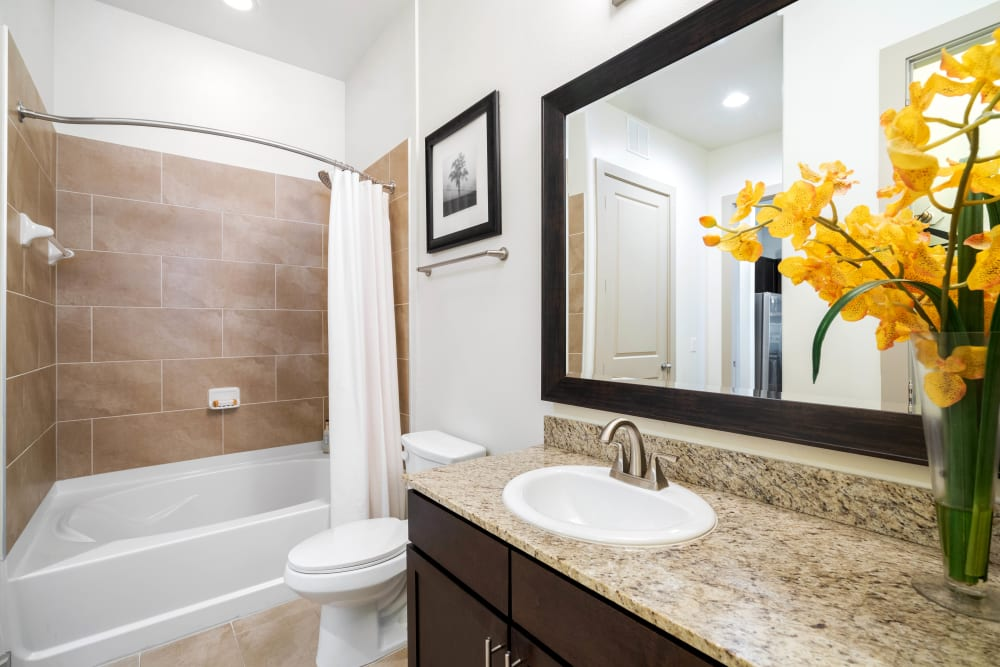 Oversized vanity mirror and a custom tiled shower in a model home's bathroom at Olympus Sierra Pines in The Woodlands, Texas