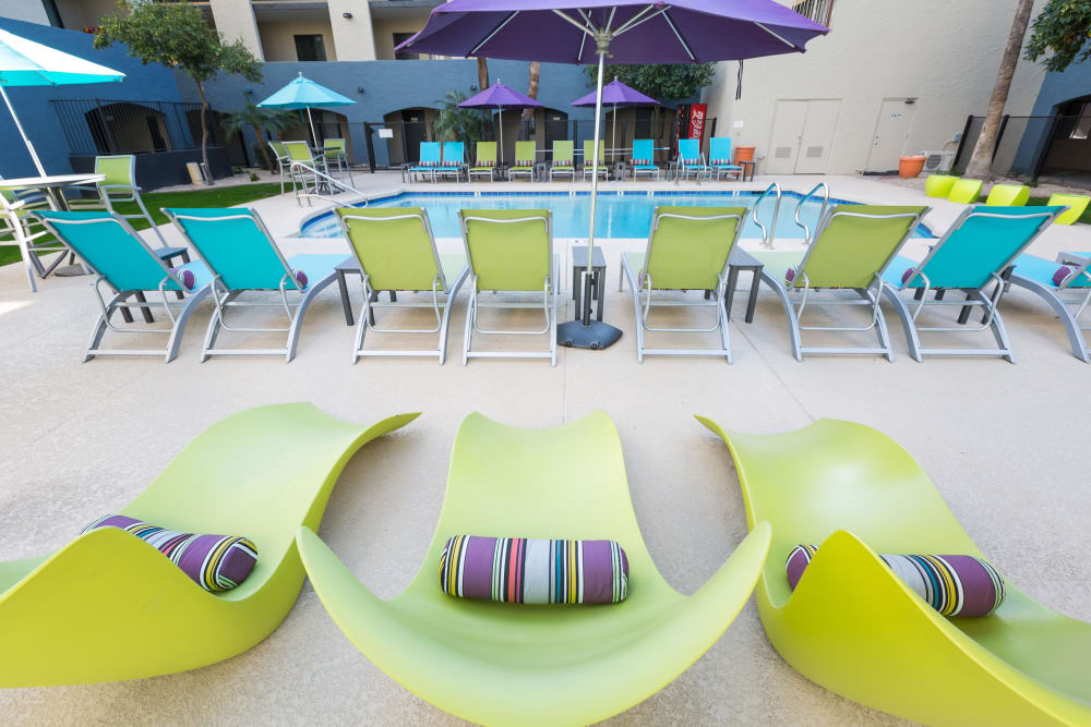One pool area with inviting and colorful lawn chairs at 4127 Arcadia in Phoenix, Arizona