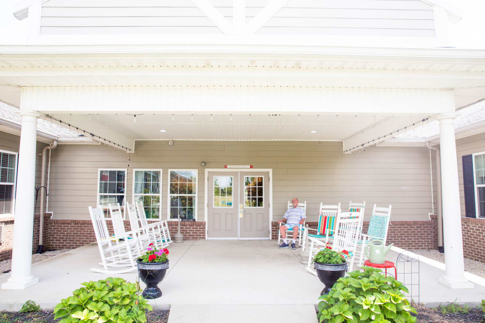 Resident enjoys a rocking chair on covered porch at Arcadian Cove in Richmond, Kentucky.