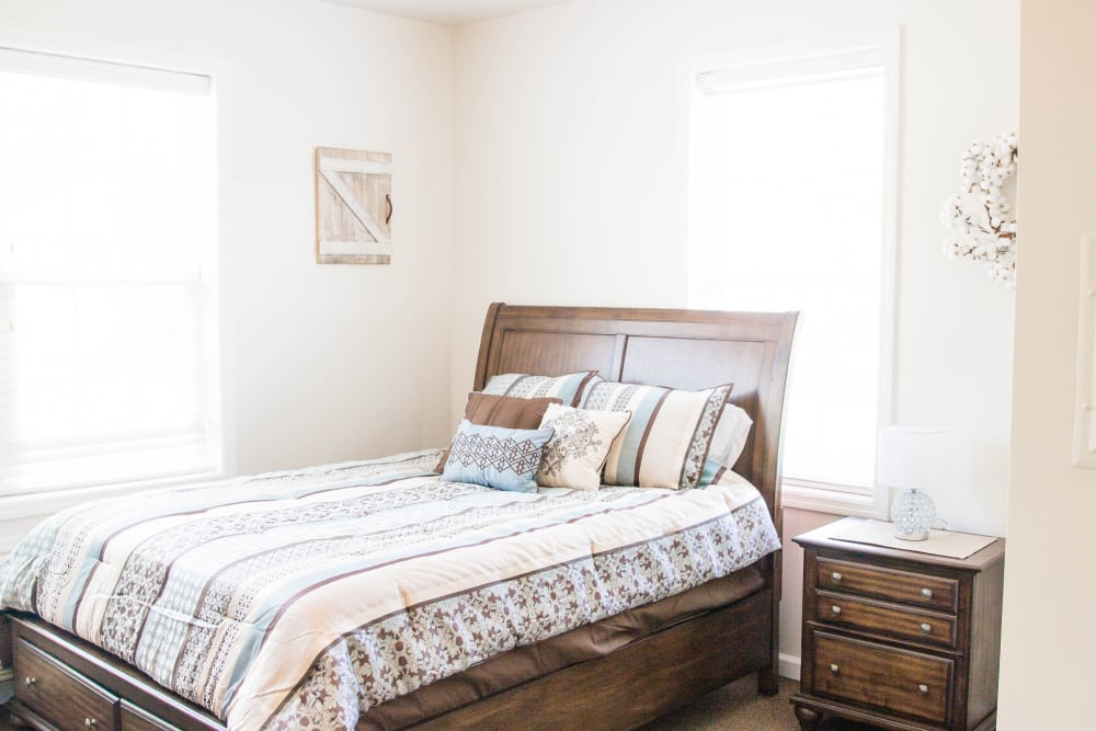 Airy bedroom with side table at Arcadian Cove in Richmond, Kentucky.