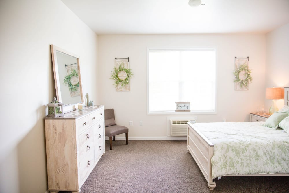 Comfortable bedroom with dresser and large window at Arcadian Cove in Richmond, Kentucky.