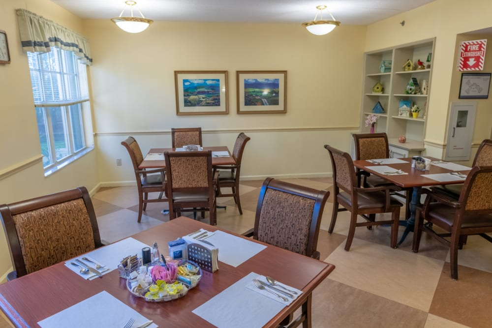 Dining tables with place settings at Village Place Senior Living in Port Charlotte, Florida