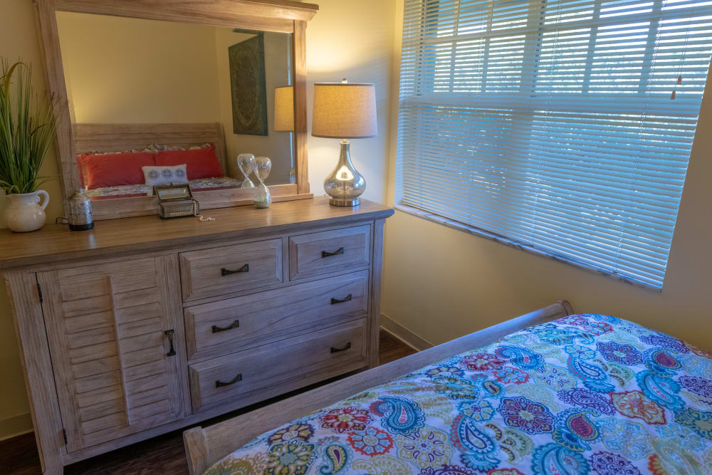 An apartment bedroom with dresser and bed at Village Place Senior Living in Port Charlotte, Florida
