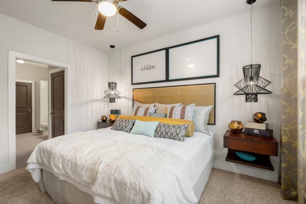 Ceiling fan and plush carpeting in a model home's bedroom at Olympus Grand Crossing in Katy, Texas