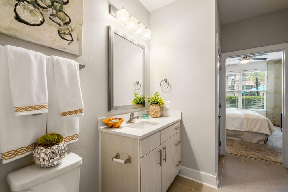 Well-lit en suite bathroom in a model home at Olympus Grand Crossing in Katy, Texas