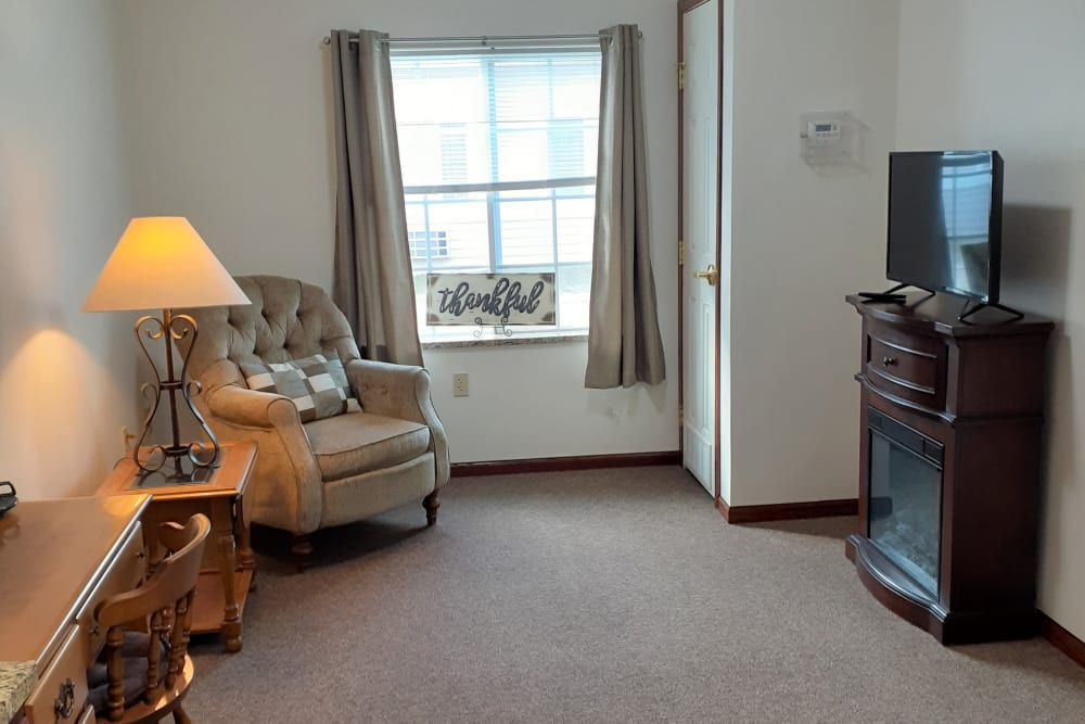Cozy living room with large window at Clover Ridge Place in Maquoketa, Iowa.