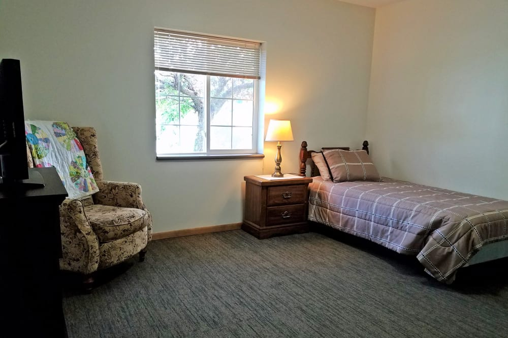 Studio apartment with bed and chair at Clover Ridge Place in Maquoketa, Iowa.