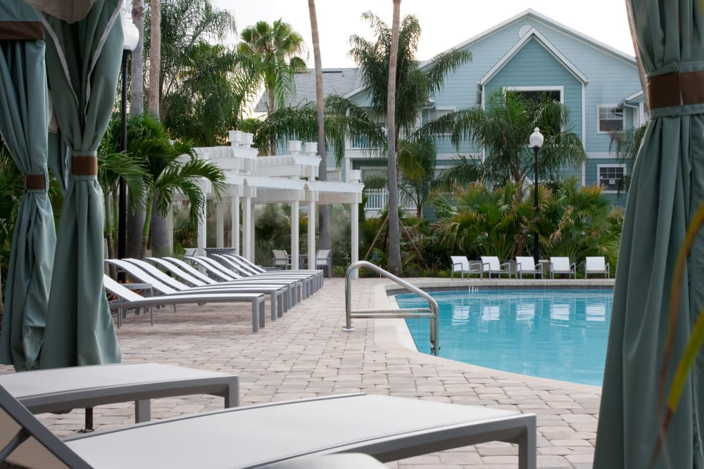 Resort-style swimming pool with cabanas nearby at Abaco Key in Orlando, Florida
