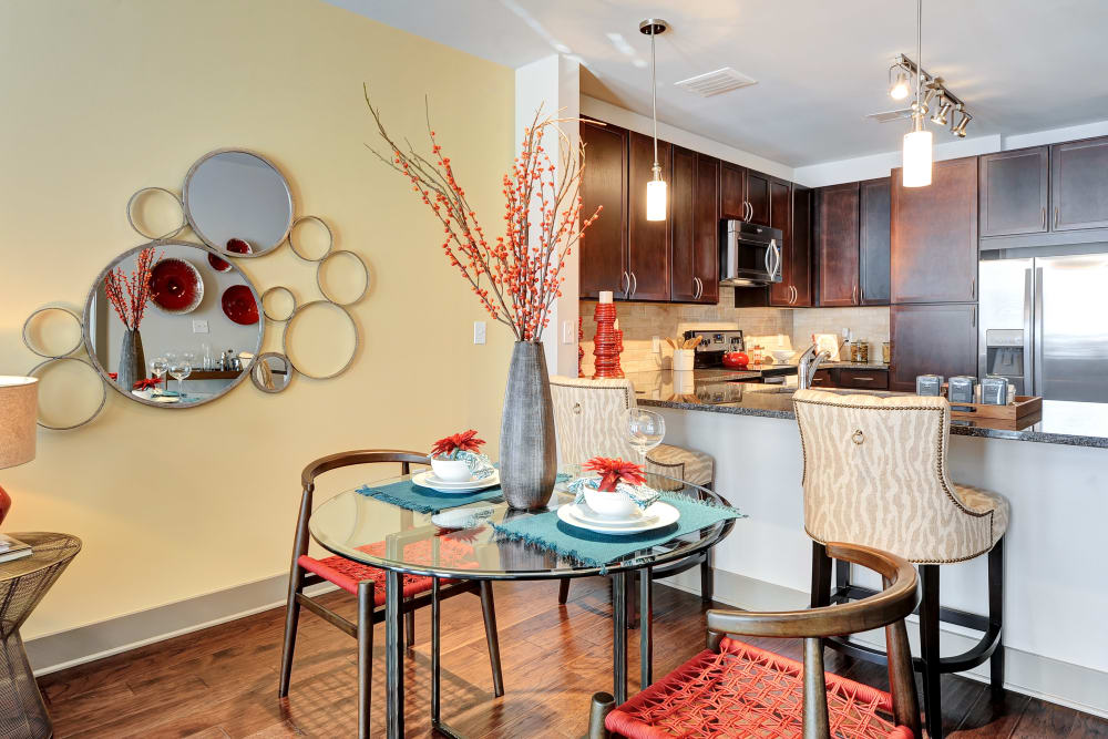 Dining area with a kitchen island at The Mark at Brickyard Apartment Homes in Beltsville, Maryland
