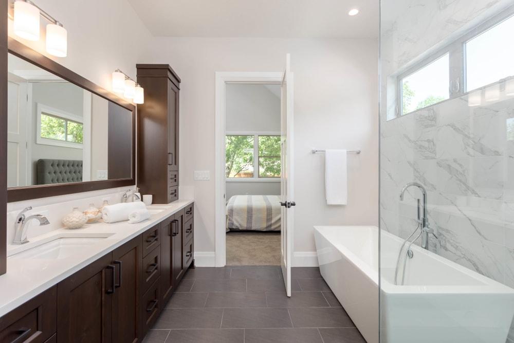 Tiled shower and granite countertop in a model home's master bathroom at El Potrero Apartments in Bakersfield, California