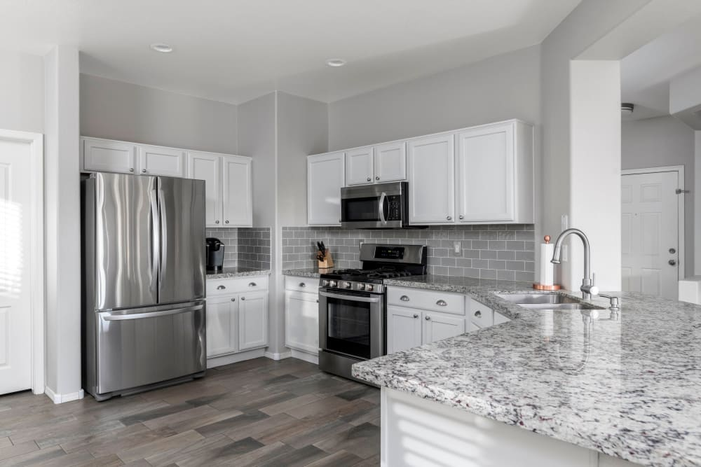 Gourmet kitchen with stainless-steel appliances in a model home at El Potrero Apartments in Bakersfield, California