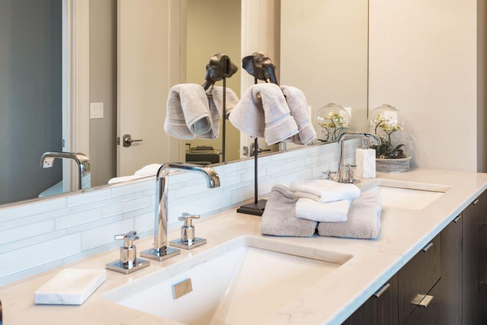 Granite countertop and modern fixtures in a model home's bathroom at El Potrero Apartments in Bakersfield, California