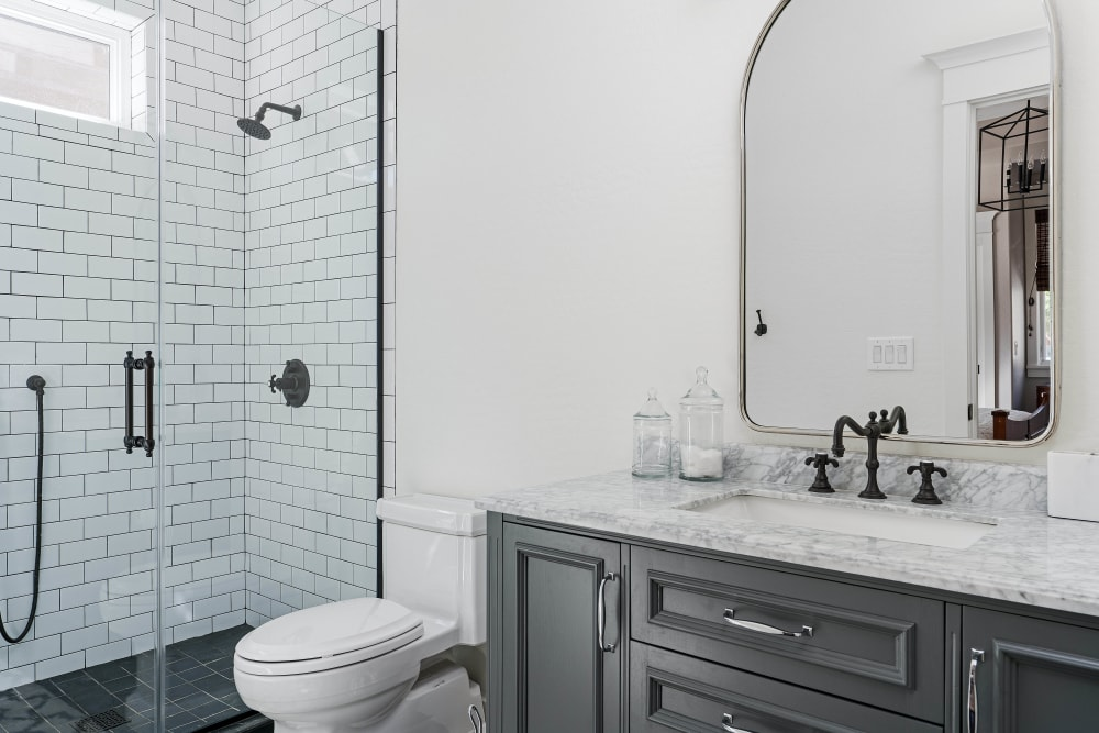 Model home's bathroom with a tiled shower at Highland View Court in Bakersfield, California