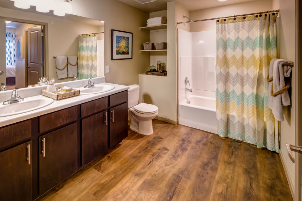 Large master bathroom with hardwood flooring in a model apartment at Granite 550 in Casper, Wyoming