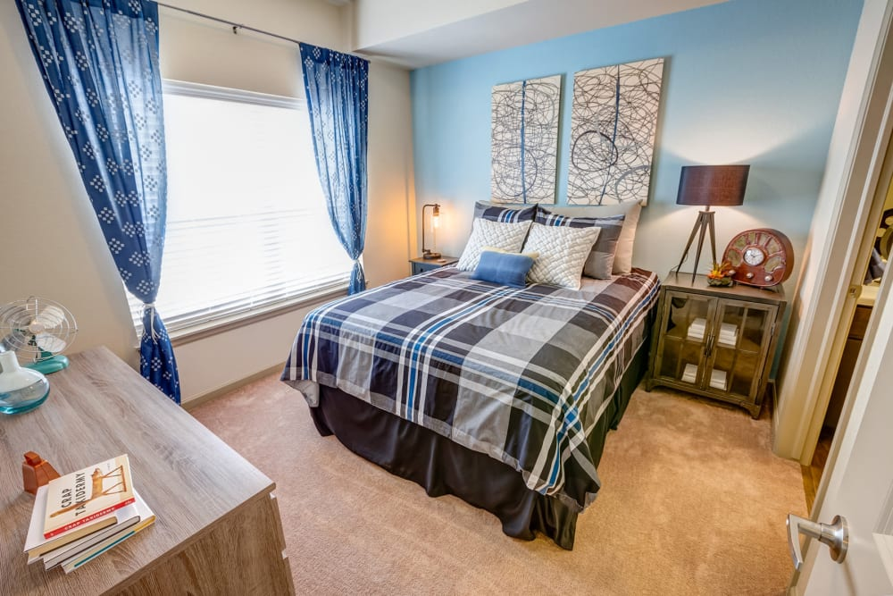 Plush carpeting and draped windows in a model apartment's bedroom at Granite 550 in Casper, Wyoming