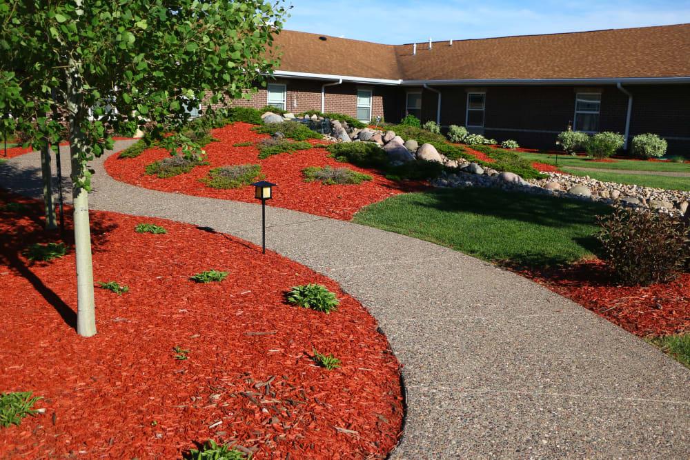 Walking path through lush landscaping at Prairie Hills Clinton in Clinton, Iowa.