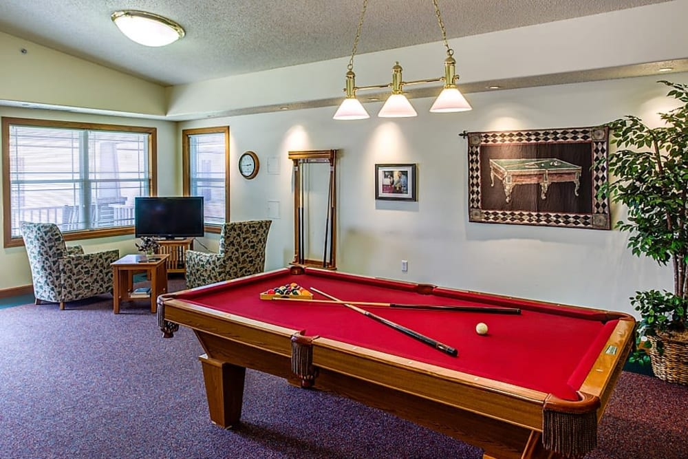 Resident game room with pool table and TV at Prairie Hills Clinton in Clinton, Iowa.