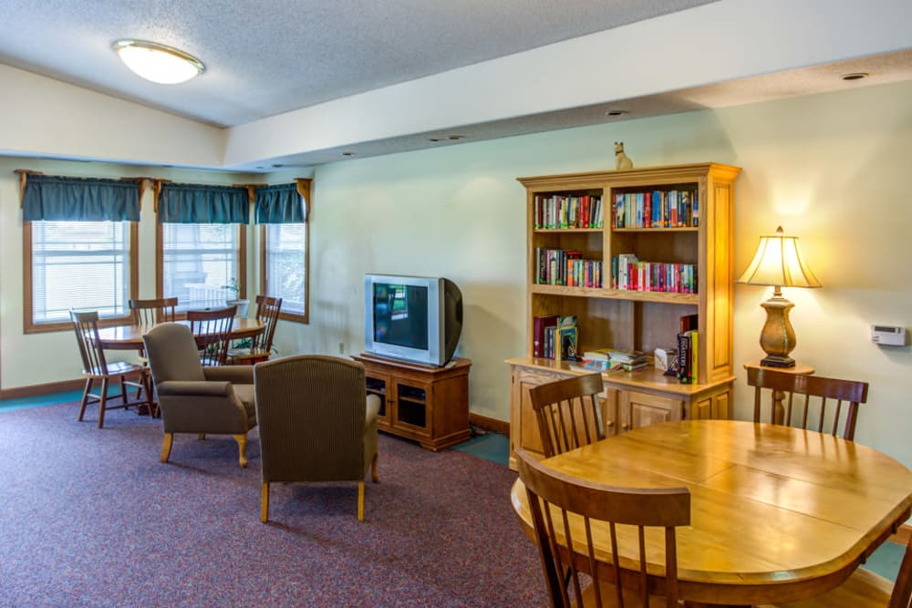 Bright community room with books and a TV at Prairie Hills in Independence, Iowa.