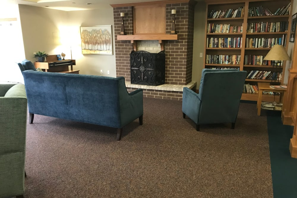 Comfortable resident lounge with books and a fireplace at Prairie Hills Senior Living in Des Moines, Iowa.