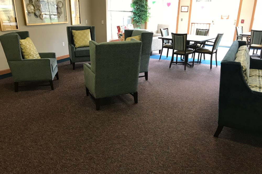 Bright resident lounge with comfortable seating and large windows at Prairie Hills Senior Living in Des Moines, Iowa.