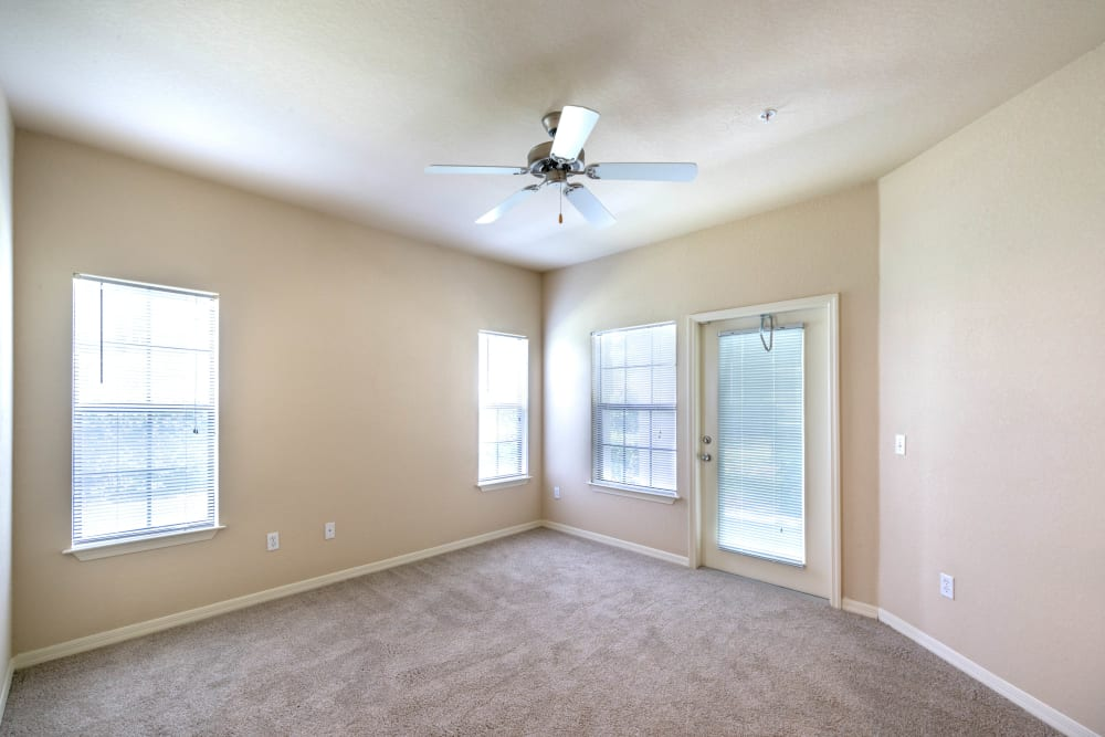 Plush carpeting and a ceiling fan in a model home's bedroom at Mirador & Stovall at River City in Jacksonville, Florida