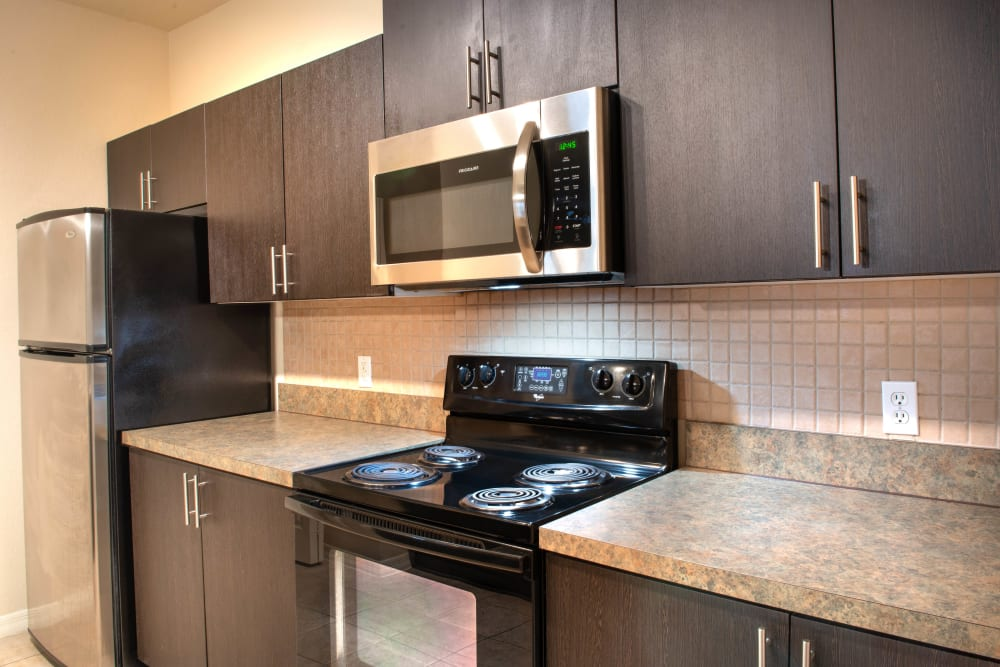 Modern kitchen with granite countertops in a model home at Mirador & Stovall at River City in Jacksonville, Florida