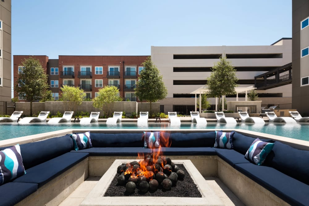 Lounge seating around the fire pit near the pool at Olympus on Main in Carrollton, Texas