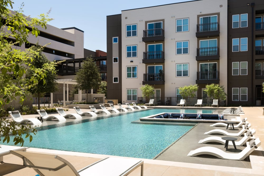 Resort-style pool with lounge chairs on the sun deck at Olympus on Main in Carrollton, Texas