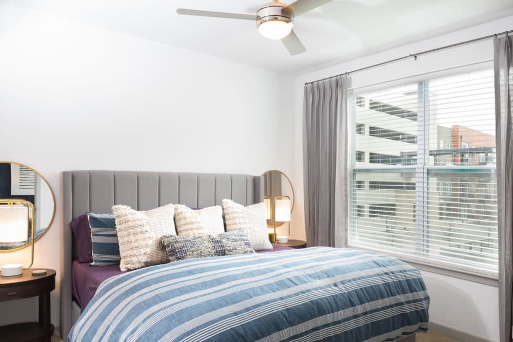 Ceiling fan and large bay windows in a model home's bedroom at Olympus on Main in Carrollton, Texas