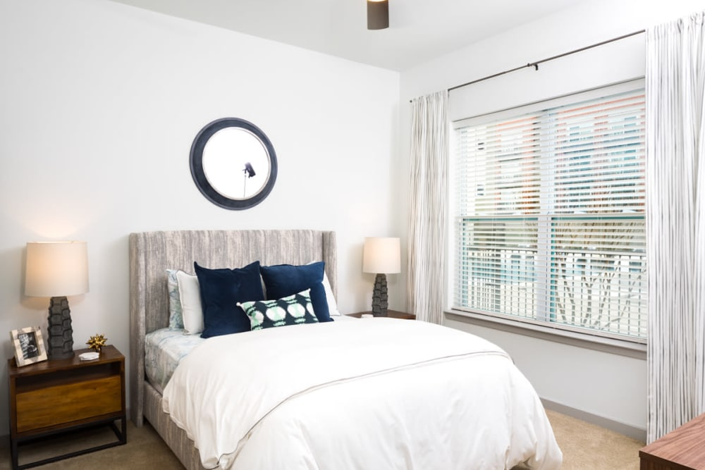 Large bay windows and a ceiling fan in a model apartment's bedroom at Lux on Main in Carrollton, Texas