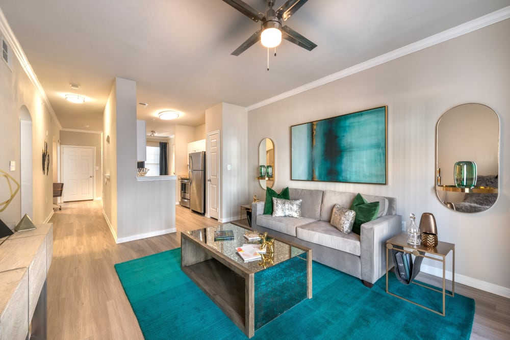 Well-furnished living area with a ceiling fan in a model home at Olympus Town Center in Keller, Texas